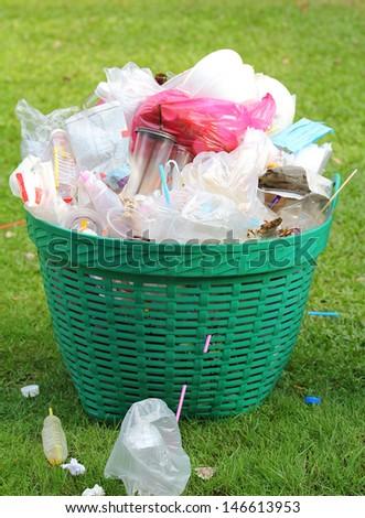 overflowing green garbage bin - stock photo