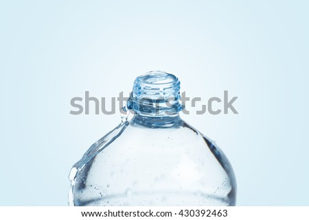 Overflowing water plastic bottle on blue background - stock photo
