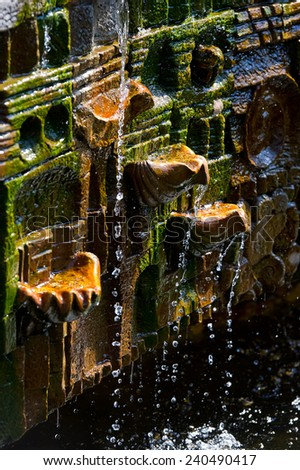 Overgrown old mossy fountain with falling drops of water - stock photo