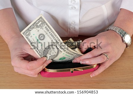 Overhead close up photo of a woman taking money out of her purse. - stock photo