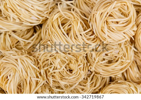 Overhead close up view of coiled, dried noodles - stock photo