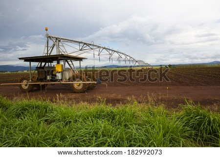 Overhead mobile powered line irrigation sprayer in recently ploughed field  - stock photo