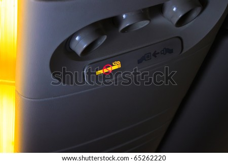 Overhead NO SMOKING sign inside an airplane - stock photo