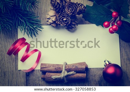 Overhead of a blank message card on oak table, bordered with natural fir cones and cinnamon, artificial holly and pine leaves, red bauble and ribbon.  Cross processed for retro or vintage effect. - stock photo