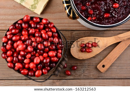 Overhead of a bucket of cranberries and a pot full of whole cranberry sauce on a rustic wooden table. Cranberry sauce is a traditional Thanksgiving side dish. Horizontal format. - stock photo