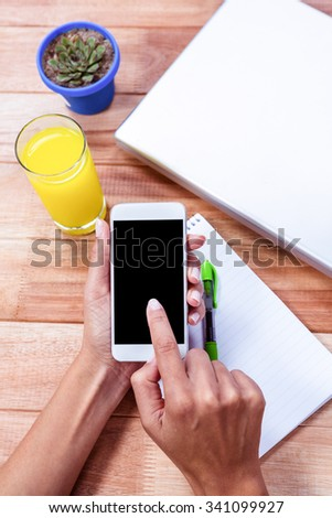 Overhead of feminine hands using smartphone with notebook, laptop and orange juice on table - stock photo