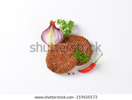 overhead of grilled burgers with vegetable side dish - stock photo