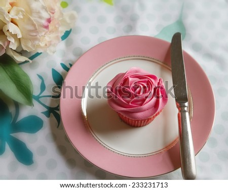 Overhead of pink rose frosted cupcake in vintage table setting - stock photo