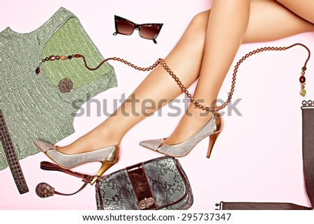 Overhead Outfit. Fashion stylish clothes set. Woman sexy legs. Essentials party accessories. Dress and clutch, necklaces, sunglasses, luxury shoes heels, creative. Unusual modern. Top view, background - stock photo