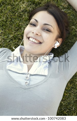 Overhead portrait of a young woman listening to music on her headphones and smiling, while laying down on green grass. - stock photo
