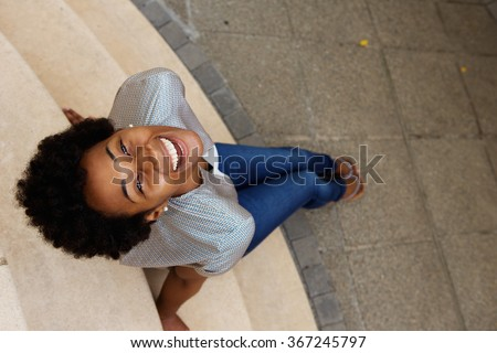 Overhead portrait of smiling young african woman sitting on steps and looking up - stock photo