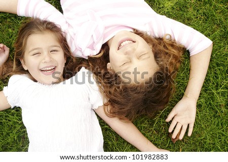 Overhead portrait of two girls laying down on green grass, laughing. - stock photo