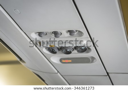Overhead seat controls of a commercial aircraft - air conditioning nozzles, reading lamps, no-smoking and seat belt on signs. Three seats. - stock photo
