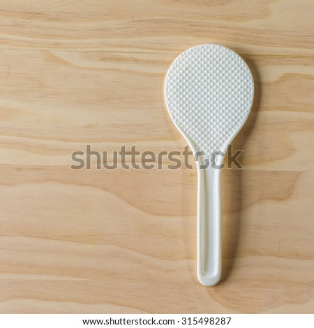 overhead shot image of plastic ladle for cooked rice on wooden background - stock photo