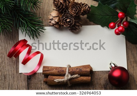 Overhead shot of a blank message card on oak table, bordered with a mixture of natural cones and cinnamon, artificial holly and pine leaves and red bauble and ribbon. - stock photo