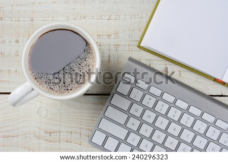 Overhead shot of a fresh brewed cup of coffee, an open book and a computer keyboard on a rustic white wood desk. Horizontal format. - stock photo
