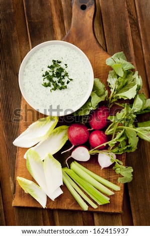 Overhead shot of a fresh herb dip surrounded by vegetables. - stock photo