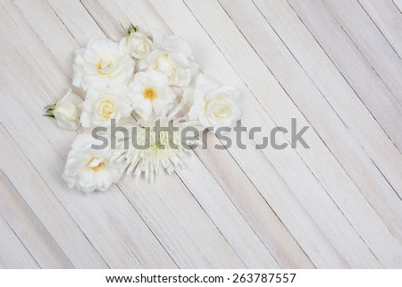 Overhead shot of a group of white flowers on a white wood table. Horizontal format with copy space. - stock photo