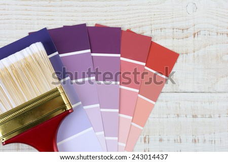 Overhead shot of a paint brush laying on color samples on a rustic white wooden surface. Horizontal format with copy space. - stock photo