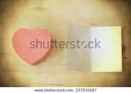Overhead shot of a pale pink wooden heart-shaped gift box next to an opened blank card, providing copy space. Fresh retro style with light, bright yellowed toning and grunge style weathering.   - stock photo