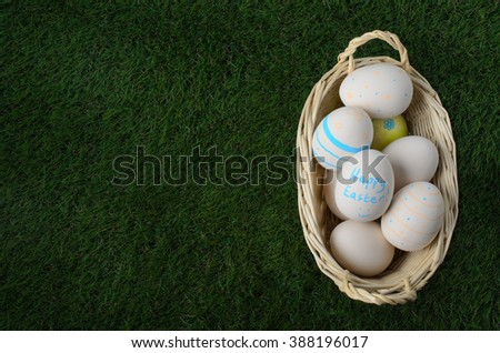 Overhead shot of a pale wicker basket filled with hand painted Easter craft eggs and set down on artificial green grass.  Copy space to the left.   - stock photo
