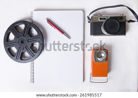 Overhead shot of a photographers workspace. A vintage film camera, film, negatives and the equipment - stock photo