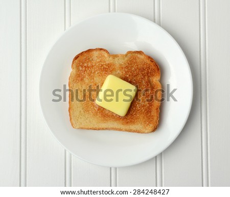 Overhead shot of a piece of buttered toast. A pat of melting butter is in the middle of the toasted white bread on a white plate  - stock photo