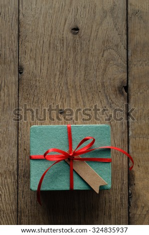 Overhead shot of a turquoise gift box on an old oak wood planked table, tied to a bow with red satin ribbon, with a blank vintage style message tag facing upwards. - stock photo