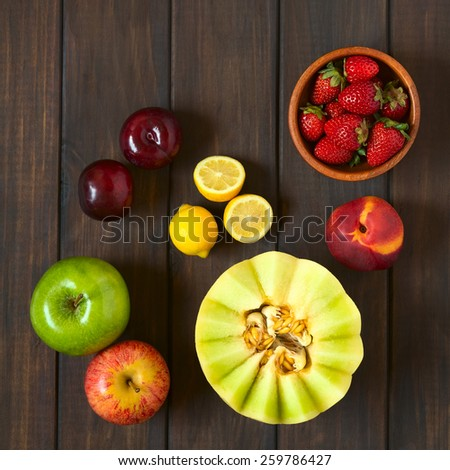 Overhead shot of a variety of fresh fruits (honeydew melon, nectarine, apple, strawberry, plum, lemon), photographed on dark wood with natural light - stock photo