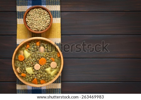 Overhead shot of a wooden bowl of lentil soup made with potato, carrot, onion and sausage slices, with small bowl of raw lentils above, photographed on kitchen towel on dark wood with natural light - stock photo