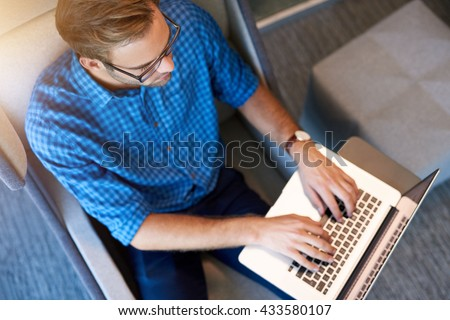 Overhead shot of a young designer typing on his laptop while working in a modern workspace - stock photo