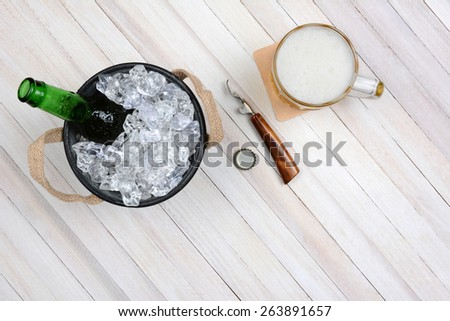 Overhead shot of an ice bucket with an opened beer bottle, a mug of beer and opener on a rustic white wood table. Horizontal format with copy space. - stock photo