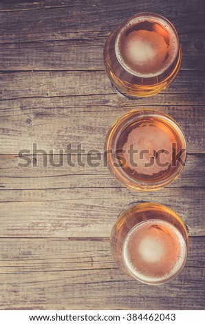 Overhead shot of beer glasses on an old wooden table - stock photo