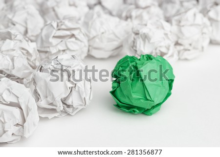 overhead shot of crumpled paper in oder and green one standing out. great idea concept on the white office table - stock photo