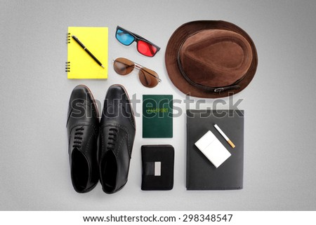 Overhead shot of hipster traveler essentials, over grey background - stock photo