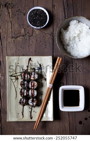 overhead shot of hosomaki sushi on plate with soy sauce and ingredients on table - stock photo