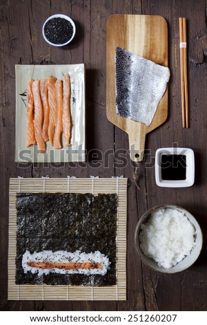 overhead shot of ingredients for preparing sushi on wooden table - stock photo