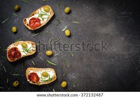 Overhead shot of mini sandwiches on dark table - stock photo