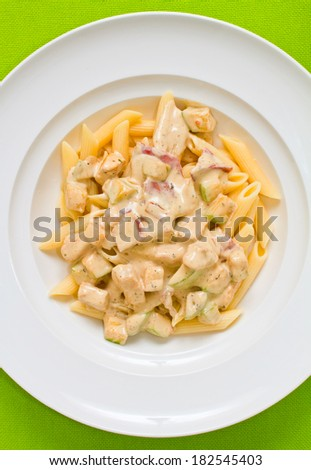 Overhead shot of penne pasta with alfredo sauce, bacon and zucchini - stock photo