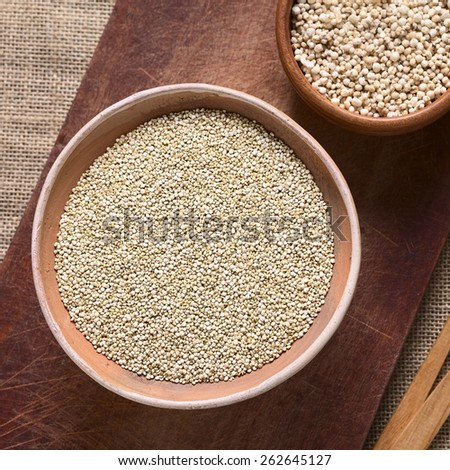 Overhead shot of raw white quinoa (lat. Chenopodium quinoa) grain seeds in bowl with popped quinoa cereal on wooden board photographed with natural light - stock photo