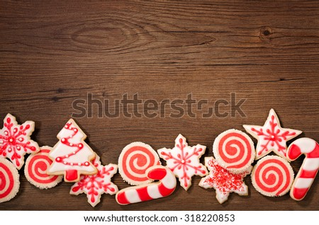 Overhead shot of red and white Christmas cookies border on a wooden background. - stock photo