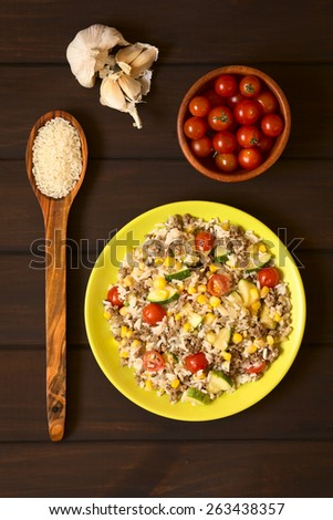 Overhead shot of rice dish with mincemeat and vegetables (sweet corn, cherry tomato, zucchini, onion) served on plate with ingredients around, photographed on dark wood with natural light - stock photo
