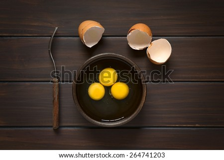 Overhead shot of three raw eggs in rustic bowl with fork on the side and broken eggshells above, photographed on dark wood with natural light - stock photo