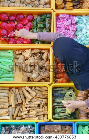 """Overhead shot over variety of delicious and colorful Malaysian home cooked local cakes or """"kueh"""" sold at street market stall in Kota Kinabalu Sabah with seller arranging the cake. - stock photo"""