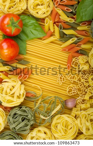 Overhead various Italian pasta background with tomatoes, basil and garlic - stock photo