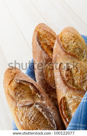 Overhead vertical shot of three fresh baked crusty French Baguettes dusted with flour and wrapped in a blue towel - stock photo