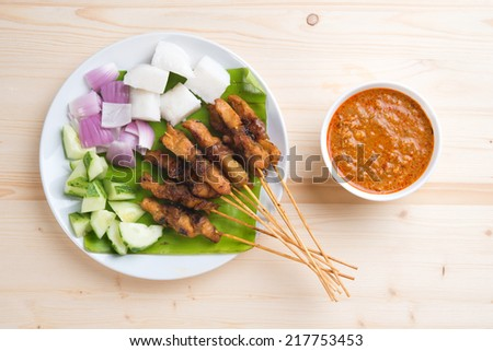 Overhead view delicious chicken satay on wooden dining table, one of famous Malaysian local dishes. - stock photo