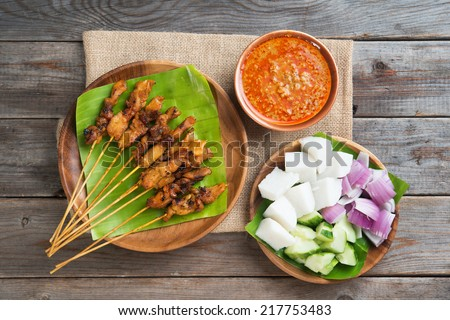 Overhead view Malaysian chicken satay with delicious peanut sauce, ketupat, onion and cucumber on wooden dining table, one of famous local dishes. - stock photo