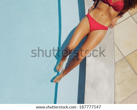 Overhead view of a beautiful female fashion model wearing red bikini resting on the edge of a pool at a luxury resort. Young caucasian lady sunbathing. - stock photo