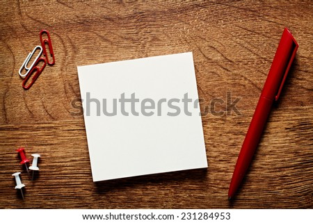 Overhead view of a blank white memo pad and pen on a wooden desk together with a paper clip and thumb tacks in a conceptual image - stock photo
